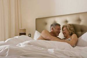 mature-couple-embracing-tenderly-in-bed-gettyimages